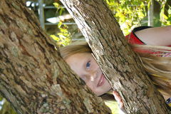 BOO!. A beautiful caucasian girl child playing hide and seek in the garden at a party Royalty Free Stock Photo