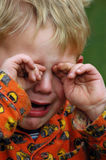 Boo Hoo. Little boy crying and wiping the tears away Stock Photos