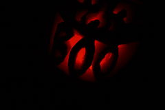 Boo Jack-O-Lantern In The Dark. A pumpkin carved into a jack-o-lantern with the word BOO for his teeth lit from inside with a candle, photographed outdoors in Stock Image