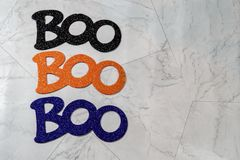 Boo word for Halloween three times, centered, isolated on marble. Glittery words in black, orange and purple royalty free stock photography