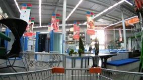 Boodschappenwagentje die zich door de supermarktdoorgangen van Domingo bewegen onder huishoudengoederen stock footage