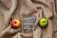 Boodschappenwagentje en appelen op juteachtergrond Stock Afbeeldingen