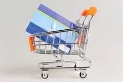 Boodschappenwagentje en creditcard binnen op grijs Stock Foto's