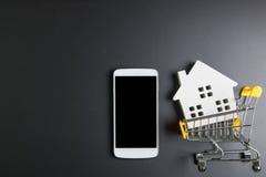 Boodschappenwagentje, Houten slangmodel en smartphone Online het winkelen concept Onroerende goederenconcept, Nieuw huisconcept H royalty-vrije stock foto
