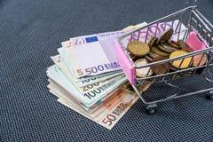 Boodschappenwagentje met Euro muntstuk met euro rekeningen wordt gevuld die Stock Afbeeldingen