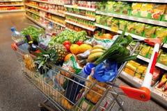 Boodschappenwagentje met fruit in supermarkt Stock Foto's