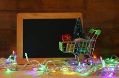 Boodschappenwagentje met Kerstmisboom naast leeg bord Royalty-vrije Stock Afbeelding
