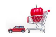 Boodschappenwagentje met rode die groene paprika door Britse auto in Engeland i wordt getrokken Stock Fotografie