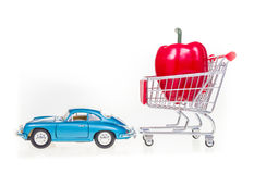 Boodschappenwagentje met rode die groene paprika door retro uitstekende auto i wordt getrokken Stock Afbeeldingen