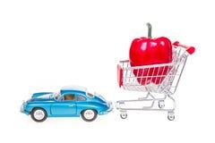Boodschappenwagentje met rode die groene paprika door retro uitstekende auto i wordt getrokken Stock Afbeelding