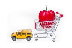 Boodschappenwagentje met rode die groene paprika door SUV- geïsoleerde auto wordt getrokken Royalty-vrije Stock Afbeeldingen