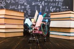 Boodschappenwagentje met schoollevering, op de lijst met boeken tegen de achtergrond van een bord Concept terug naar school stock foto