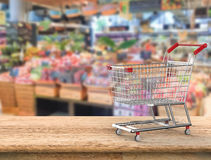 Boodschappenwagentje met supermarktachtergrond Stock Afbeeldingen