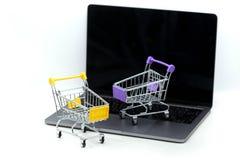 Boodschappenwagentje op laptop, concept over online aankoop en winkel stock afbeelding