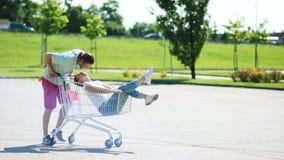 Boodschappenwagentje op parkeren Een paar jonggehuwden berijden in een het winkelen mand dichtbij een supermarkt Pret, grap, vreu stock video