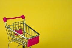Boodschappenwagentje of supermarktkarretje op gele achtergrond, busin Stock Foto's