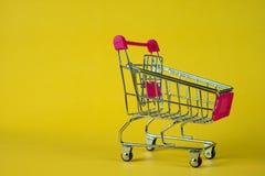 Boodschappenwagentje of supermarktkarretje op gele achtergrond, busin Stock Afbeeldingen