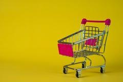 Boodschappenwagentje of supermarktkarretje op gele achtergrond, busin Royalty-vrije Stock Afbeeldingen