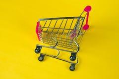 Boodschappenwagentje of supermarktkarretje op gele achtergrond, busin Royalty-vrije Stock Foto