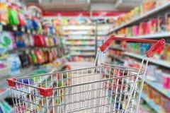 Boodschappenwagentje in supermarktsteeg Stock Afbeeldingen