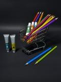 Boodschappenwagentjehoogtepunt met artistieke goederen voor zich het terugtrekken op zwarte Stock Afbeelding