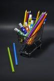 Boodschappenwagentjehoogtepunt met artistieke goederen voor zich het terugtrekken op zwarte Stock Foto's