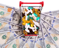 Boodschappenwagentjehoogtepunt met pillen en capsules over dollarrekeningen Royalty-vrije Stock Foto's
