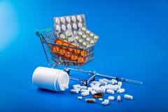 boodschappenwagentjehoogtepunt van drug en geneeskundepillen op blauw stock foto