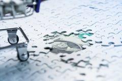 Boodschappenwagentjehoogtepunt van puzzel op de achtergrond van de gelddollar, Royalty-vrije Stock Fotografie
