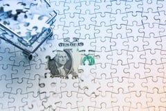 Boodschappenwagentjehoogtepunt van puzzel op de achtergrond van de gelddollar, Royalty-vrije Stock Foto's