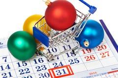 Boodschappenwagentjes en Kerstmisballen op kalender Stock Foto's