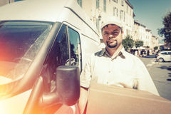Boodschapper Delivering Parcel, die zich naast Zijn Bestelwagen bevinden stock afbeeldingen