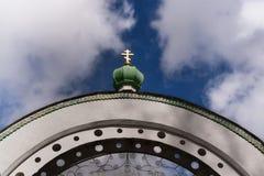 Boog en groene koepel met een Gouden kruis op blauwe hemel tussen Stock Foto's
