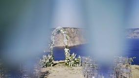 Boog en stoelen voor huwelijk bij kust stock video