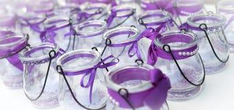 Boog-gebonden purpere linten op de houders van de glaskaars Stock Foto