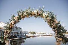 Boog met bloemen voor de huwelijksceremonie wordt verfraaid in de jachtclub die stock fotografie