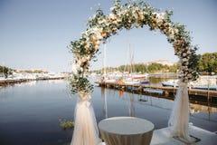 Boog met bloemen voor de huwelijksceremonie wordt verfraaid in de jachtclub die stock foto's