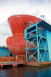 Boog van grote rode tanker onder het herstellen in drijvend dok Stock Foto