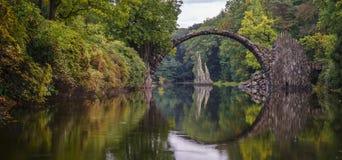 Boogbrug in Kromlau, Saksen, Duitsland De kleurrijke herfst in Kiem royalty-vrije stock fotografie