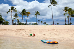 Boogie board and beach balls on a tropical beach Stock Photos