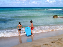 Boogie Board Kids. Brother and sister entering the ocean with a boogie board Stock Photography