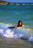 Boogie Boarding. A woman rides a wave with a boogie board on a maui beach Royalty Free Stock Photos