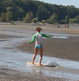 Boogie Boarding. Teenage girl sand surfing at the beach stock photo