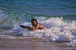 Boogie Boarding on Maui. A woman having fun on a boogie board on a maui beach Stock Images