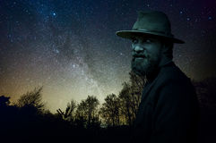 Boogie man in the forest. Scary man in hat and beard at night in a creepy forest Royalty Free Stock Photo
