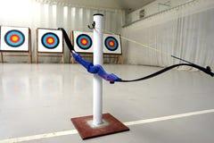 Boogschietenboog het hangen op zijn tribune, met doelstellingen op achtergrond Stock Afbeelding