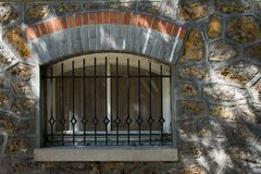 Boogvormig die grondvenster met rooster op een bakstenen muur Parijs, Frankrijk wordt behandeld royalty-vrije stock afbeelding