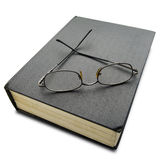 Book. A pair of reading glasses on thick hard cover black book on white - with clipping path Stock Image