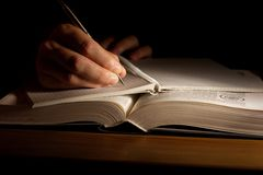 Book. Hand with pen taking notes from an open book Royalty Free Stock Image