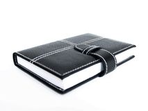 Book 4. Black leather cased notebook, on white bacground with pen for writing Stock Images